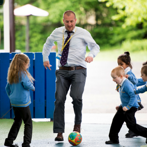 Teacher playing football with children